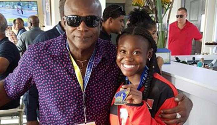 Hasely Crawford, Olympic 100 metres gold medallist, congratulates double gold medalist Khalifa St Fort at the Flow Carifta Games in Curacao, yesterday.