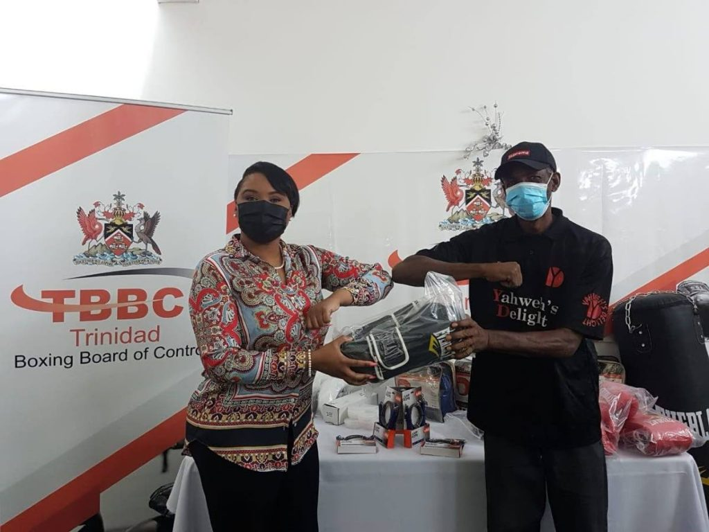 Minister of Sport and Community Development Shamfa Cudjoe, left, presents boxing gears and equipment to head coach of the Wallerfield Warriors Boxing Gym Waldron Brooks. -